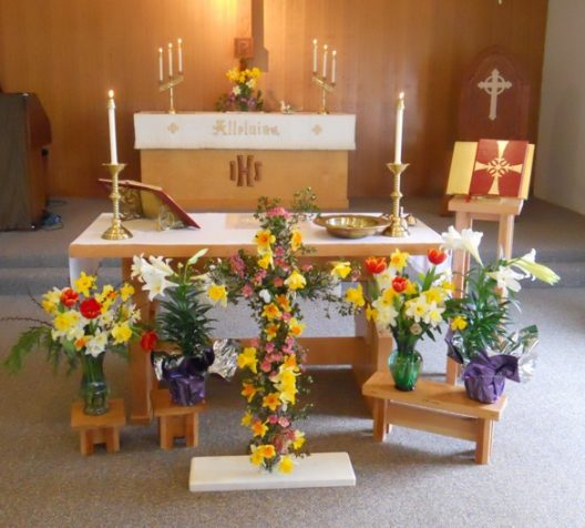 The beautiful Altar Table with the flower offerings in front.